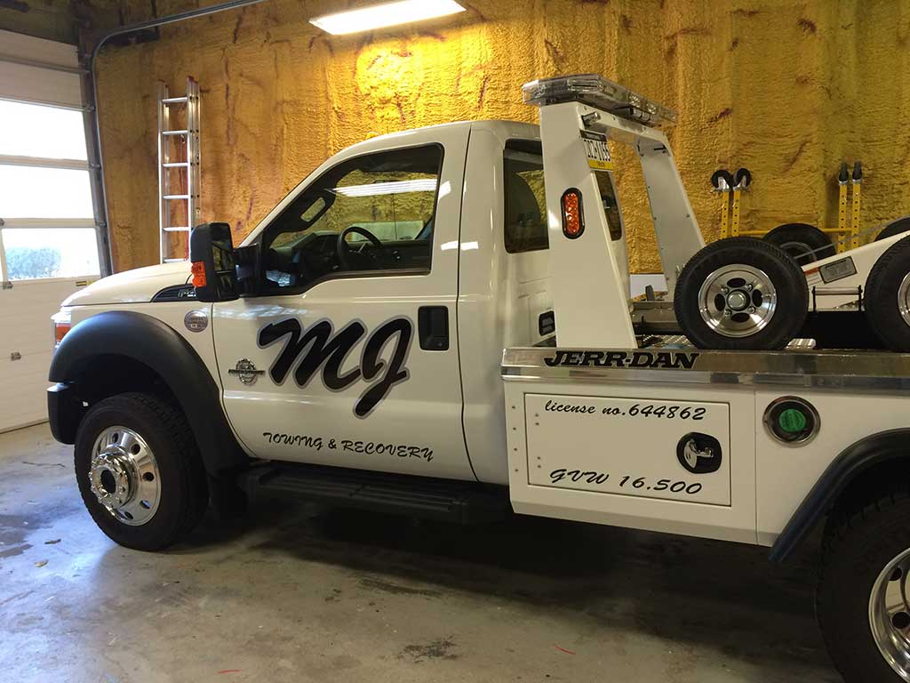 MJ Repo Services tow truck parked inside company's garage